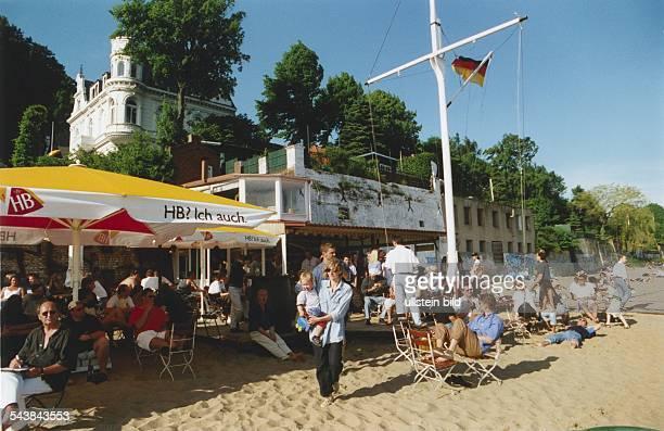 Gäste auf Stühlen und im Sand in der Strandperle an der Elbe der InTreff in Övelgönne Undatiertes Foto