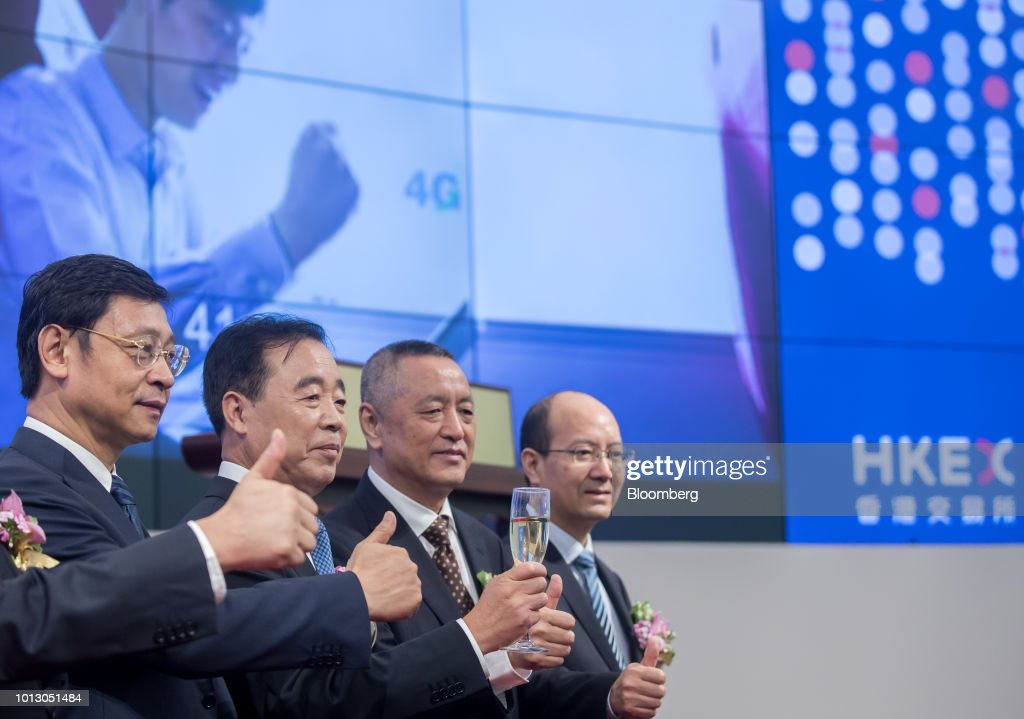 Gu Xiaomin, deputy general manager at China Tower Corp., from left, Tong Jilu, chairman, Gao Buwen, deputy general manager, and Gao Chunlei, chief accountant, pose for photographs during the company's listing ceremony at the Hong Kong Stock Exchange in Hong Kong, China, on Wednesday, Aug. 8, 2018. China Tower inched up in Hong Kong trading debut after completing the world's largest initial public offering in two years. Photographer: Paul Yeung/Bloomberg via Getty Images