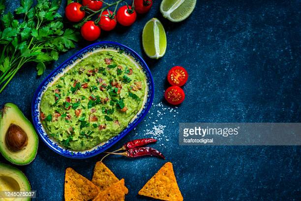 guacamole and chips on bluish tint table. copy space - guacamole stock pictures, royalty-free photos & images