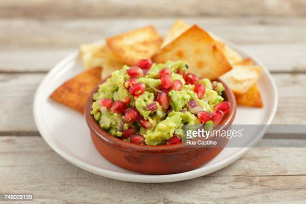 guacamole with pomegranate seeds and tortilla chips - rua fotografías e imágenes de stock