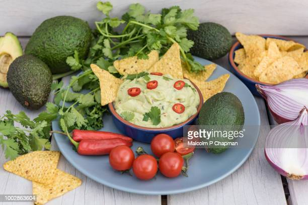 guacamole (avocado dip) with tortilla corn chips, avocado, tomatoes, red onion and chilli peppers. - guacamole stock pictures, royalty-free photos & images