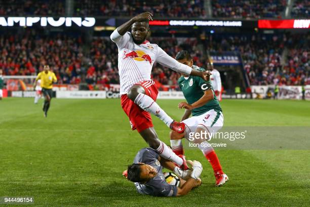 Guadalajara goalkeeper Rodolfo Cota makes a save as New York Red Bulls defender Kemar Lawrence jumps over him during the second half of the CONCACAF...
