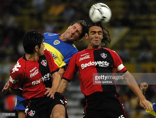 Denis Caniza y Fabricio Fuentes del Atlas de Guadalajara disputan el balon con Martin Palermo de Boca Juniors de Argentina durante un partido...