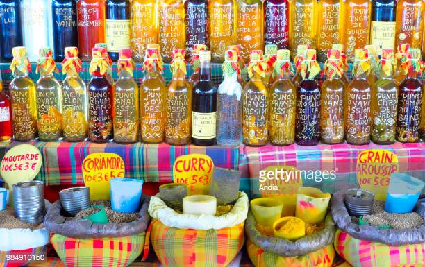 bottles of punch rhum arrange on a stall at La Darse covered market and spices