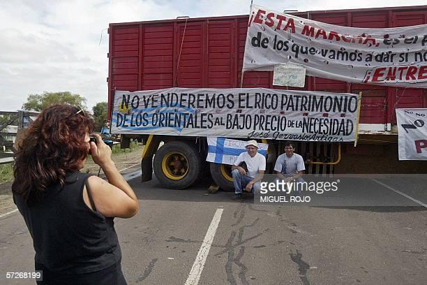 Gualeguaychu, URUGUAY: Una turista toma fotos de familiares frente a un acoplado con pancartas colocado por ambientalistas argentinos para cortar la...
