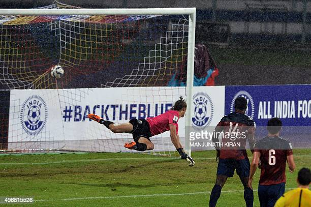 Guam goalkeeper Douglas Herrick attempts a save as India's forward Robin Singh scores a goal during the the Asia Group D FIFA World Cup 2018...