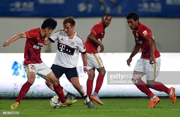 Guangzhou Evergrande's Chinese defender Zou Zheng and Bayern Munich's midfielder Mario Goetze vie for the ball during a friendly football match...