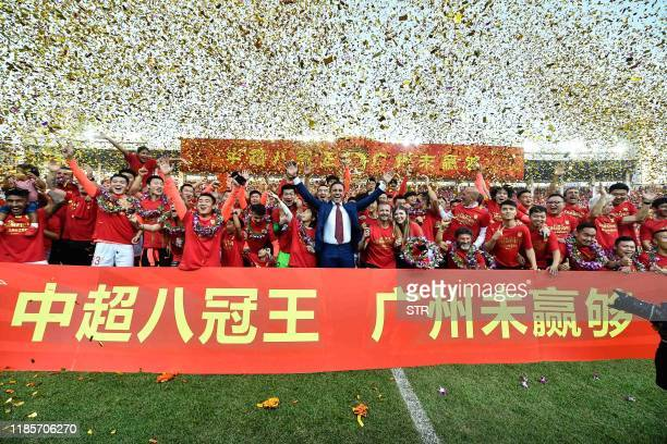 Guangzhou Evergrande's head coach Fabio Cannavaro players and staff members celebrate after defeating Shanghai Shenhua to win the Chinese Super...