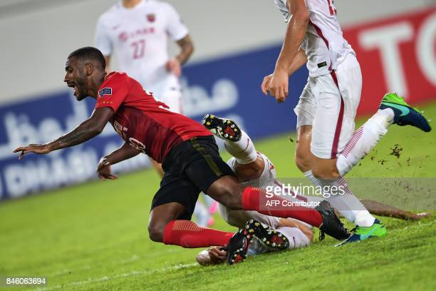 TOPSHOT Guangzhou Evergrande's Muriqui falls as he fights for the ball during their AFC Champions League quarterfinal football match against Shanghai...