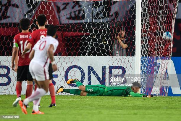 Guangzhou Evergrande's Zeng Cheng fails to save the ball for a goal by Shanghai SIPG's Hulk during their AFC Champions League quarterfinal football...