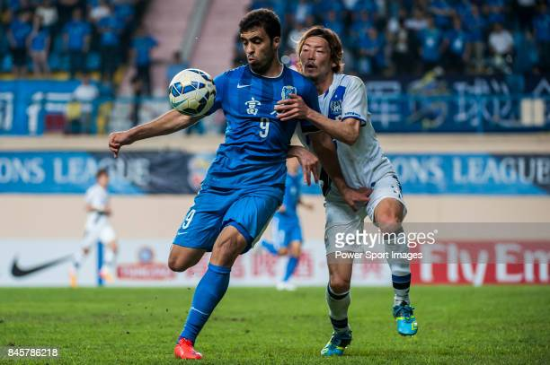 Guangzhou RF forward HamedAllah Abderrazzaq fights for the ball with Gamba Osaka defender Fujiharu Hiroki during the 2015 AFC Champions League Group...