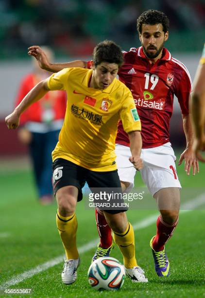 Guangzhou's Chinese mildfielder Dario Conca is defended by Al Ahly's Egyptian mildfielder Abdallah Said during their FIFA Club World Cup quarter...