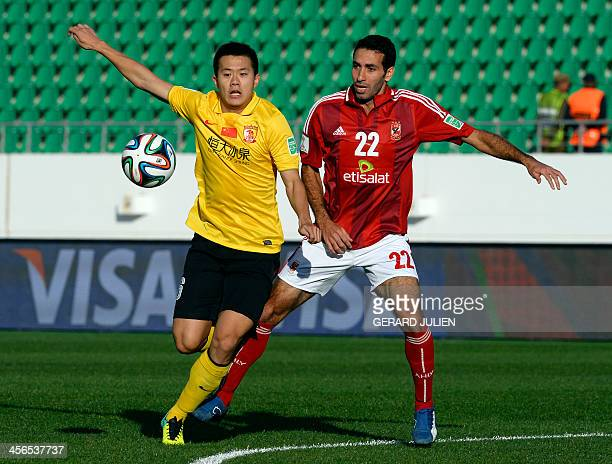Guangzhou's Chinese mildfielder Huang Bowen is defended by Al Ahly's Egyptian mildfielder Mohamed Aboutrika during their FIFA Club World Cup quarter...