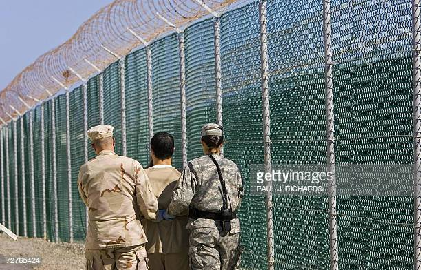 A detainee is escorted by military guards to his annual Admistrative Review Board hearing inside Camp Delta's Maximum Security area 06 December 2006...