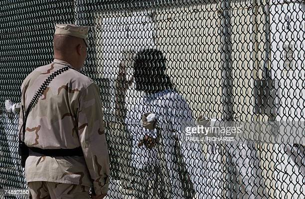In this 24 April 2007 file photo a Joint Task Force guard at Camp Delta in Guantanamo Bay Naval Station Cuba talks with a detainee who has had his...