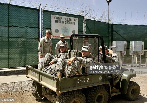 In this photo reviewed by a US Department of Defense official men in US military uniform on an allterrain vehicle pass one saluting an officer by the...