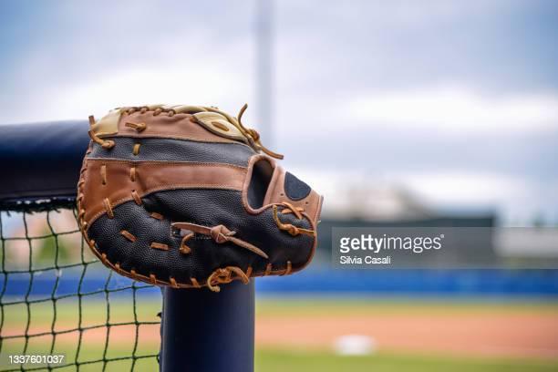 guanto da baseball appoggiato a ringhiera del dugout - silvia casali stock pictures, royalty-free photos & images
