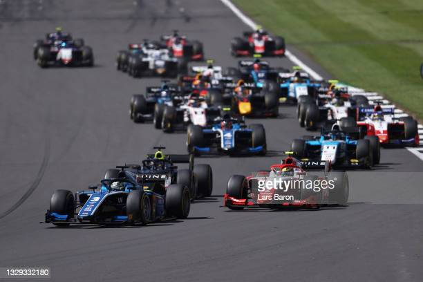 Guanyu Zhou of China and UNI-Virtuosi Racing leads Oscar Piastri of Australia and Prema Racing and the rest of the field round turn one at the start...