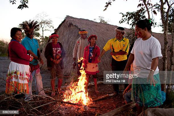 Guarani community male and female standing around a fire at dusk The Guarani are one of the most populous indigenous populations in Brazil but with...