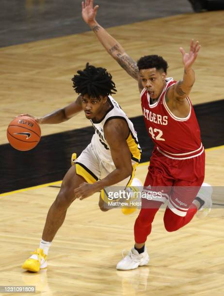 Guard Ahron Ullis of the Iowa Hawkeyes drives down the court during the second half against guard Jacob Young of the Rutgers Scarlet Knights at...