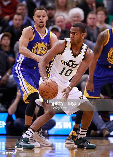 Guard Alec Burks of the Utah Jazz pass the ball as Golden State Warriors guard Stephen Curry defends during a game against the Utah Jazz during the...