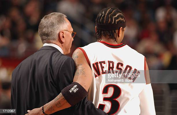 Guard Allen Iverson of the Philadelphia 76ers and head coach Larry Brown put their arms around each other as they walk on the court during the game...