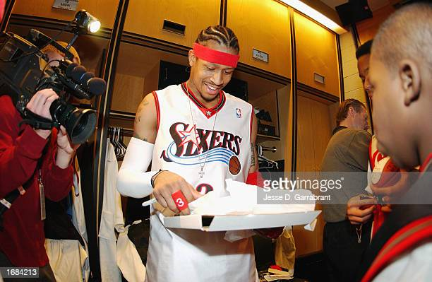 Guard Allen Iverson of the Philadelphia 76ers smiles as he looks at a photo before autographing it for a child as part of the NBA Make a Wish...