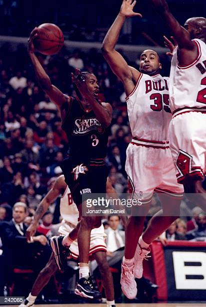 Guard Allen Iverson of the Philadelphia 76ers tries to get the ball past forward Jason Caffey and Scott Burrell of the Chicago Bulls during a game at...