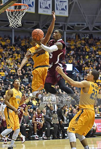 Guard Anthony Beame of the Southern Illinois Salukis drives to the basket between defenders Fred Van Vleet and Tekele Cotton of the Wichita State...
