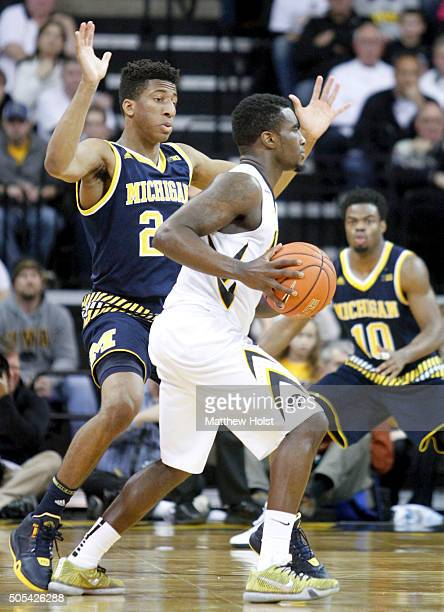 Guard Anthony Clemmons of the Iowa Hawkeyes brings the ball down the court against guardAubrey Dawkins of the Michigan Wolverines in the second half...