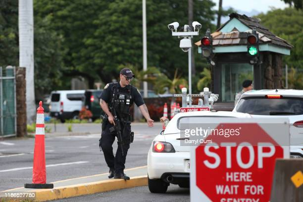 A guard armed with an assault rifle checks vehicles entering the Nimitz Gate entrance of Joint Base Pearl Harbor Hickam on December 4 2019 in...