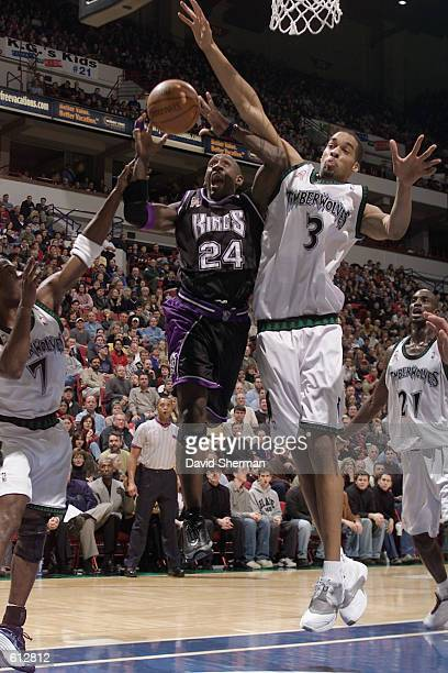 Guard Bobby Jackson of the Sacramento Kings shoots past center Loren Woods of the Minnesota Timberwolves during the NBA game at Target Center in...