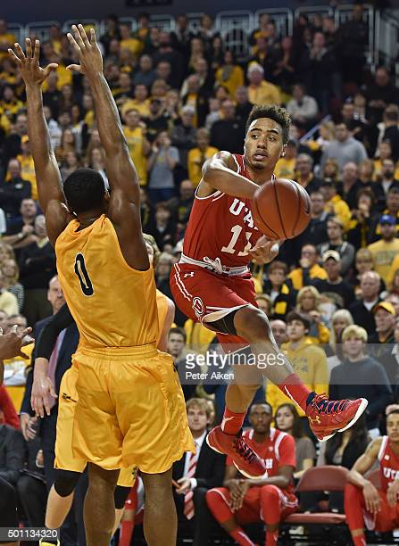 Guard Brandon Taylor of the Utah Utes passes the ball around defender Rashard Kelly of the Wichita State Shockers during the second half on December...