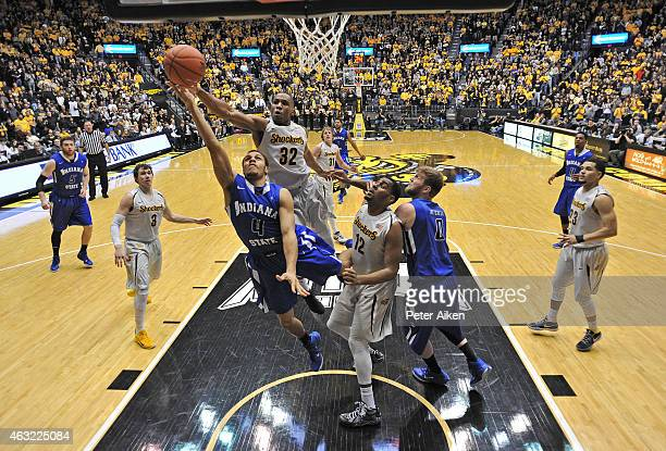 Guard Brenton Scott of the Indiana State Sycamores drives to the basket against defenders Tekele Cotton and Darius Carter Jr #12 of the Wichita State...