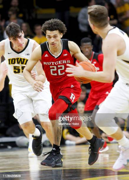 Guard Caleb McConnell of the Rutgers Scarlet Knights drives down the court in the first half between guard Jordan Bohannon and forward Luka Garza of...