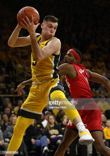 Guard C.J. Fredrick of the Iowa Hawkeyes grabs a rebound in the first half in front of guard Dachon Burke of the Nebraska Cornhuskers, at...