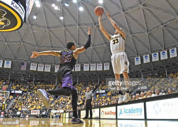 Guard Conner Frankamp of the Wichita State Shockers hits a threepoint shot over guard Jordan Ashton of the Northern Iowa Panthers during the first...