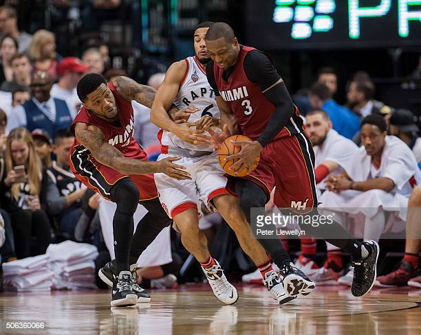 Guard Cory Joseph of the Toronto Raptors gets caught between forward Udonis Haslem and guard Dwayne Wade of the Miami Heat in the fourth quarter at...