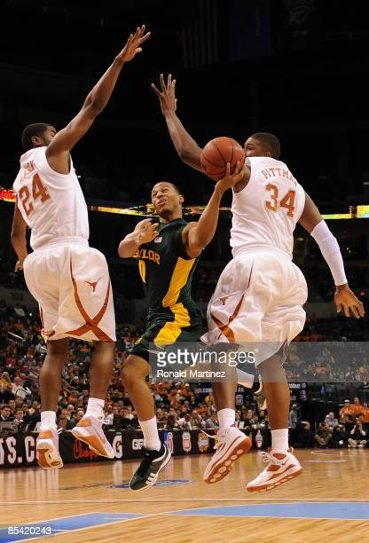 Guard Curtis Jerrells of the Baylor Bears goes up for a shot against Justin Mason and Dexter Pittman of the Texas Longhorns during the Phillips 66...