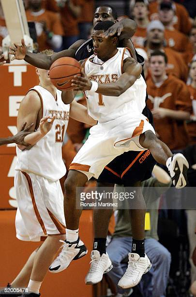 Guard Daniel Gibson of the Texas Longhorns passes the ball in front of Ivan McFarlin of the Oklahoma State Cowboys on January 17 2005 at the Frank...