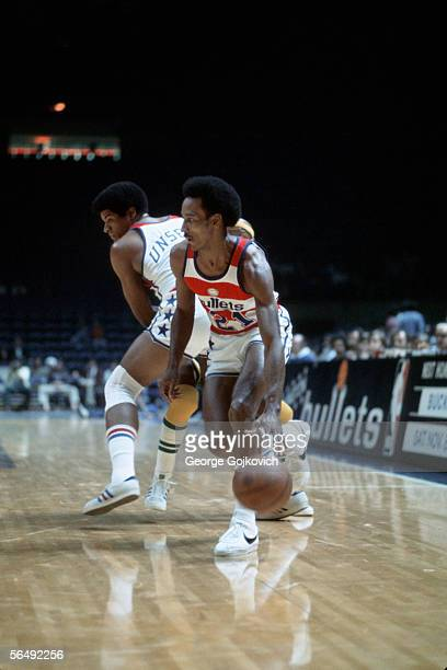 Guard Dave Bing of the Washington Bullets dribbles the ball past center Wes Unseld during a National Basketball Association game at the Capital...