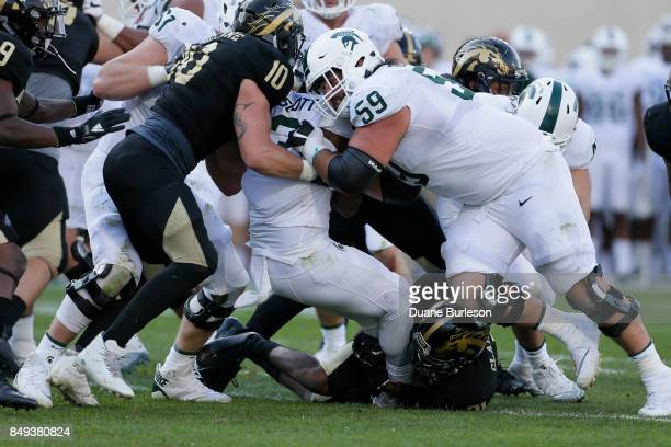 Guard David Beedle of the Michigan State Spartans tries to block linebacker Robert Spillane of the Western Michigan Broncos as running back LJ Scott...