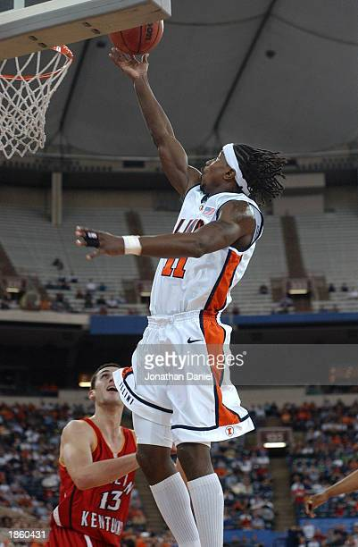 Guard Dee Brown of Illinois hits a break-away layup over guard Filip Videnov of Western Kentucky in the 1st round of the NCAA Tournament on March 20,...