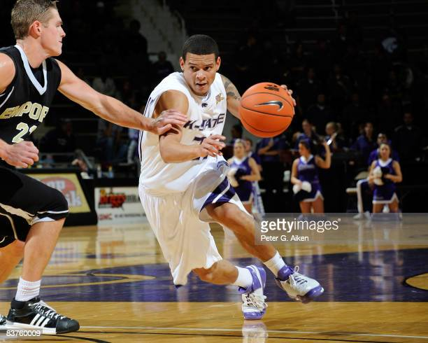 Guard Denis Clemente of the Kansas State Wildcats drives around pressure from guard Dustin Andrews of the Emporia State Hornets durng the second half...