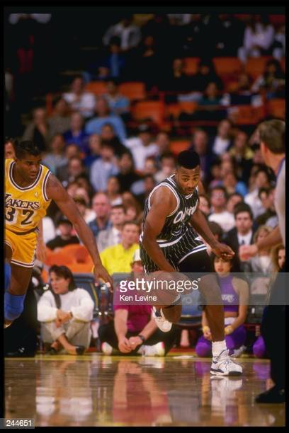 Guard Dennis Scott of the Orlando Magic dribbles the ball down the court as guard Magic Johnson of the Los Angeles Lakers chases after him during a...