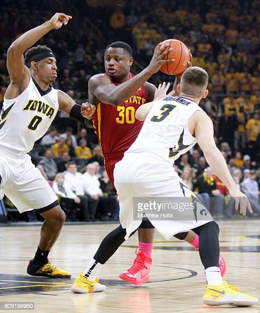 Guard Deonte Burton of the Iowa State Cyclones goes to the basket during the first half against forward Ahmad Wagner and guard Jordan Bohannon of the...