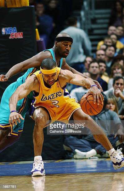 Guard Derek Fisher of the Los Angeles Lakers backs in against guard Baron Davis of the New Orleans Hornets during the game at Staples Center on...