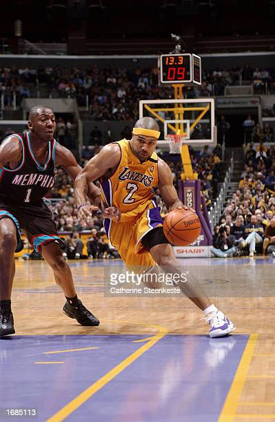Guard Derek Fisher of the Los Angeles Lakers drives past guard Wesley Person of the Memphis Grizzlies during the game at Staples Center on December 3...