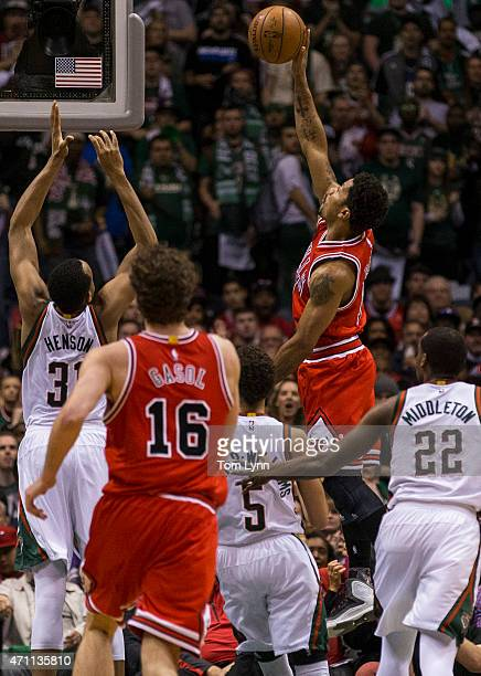 Guard Derrick Rose of the Chicago Bulls shoots over center John Henson of the Milwaukee Bucks in the first quarter of game four of the first round of...