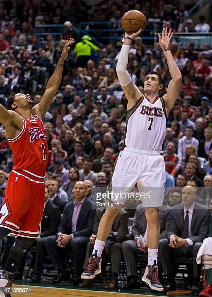 Guard Derrick Rose of the Chicago Bulls tries to block the shot of Ersan Ilyasova of the Milwaukee Bucks in the first quarter of game four of the...
